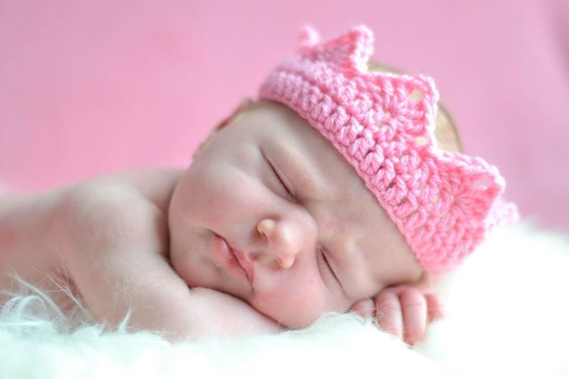 Close-up of new born baby girl in crown sleeping on bed