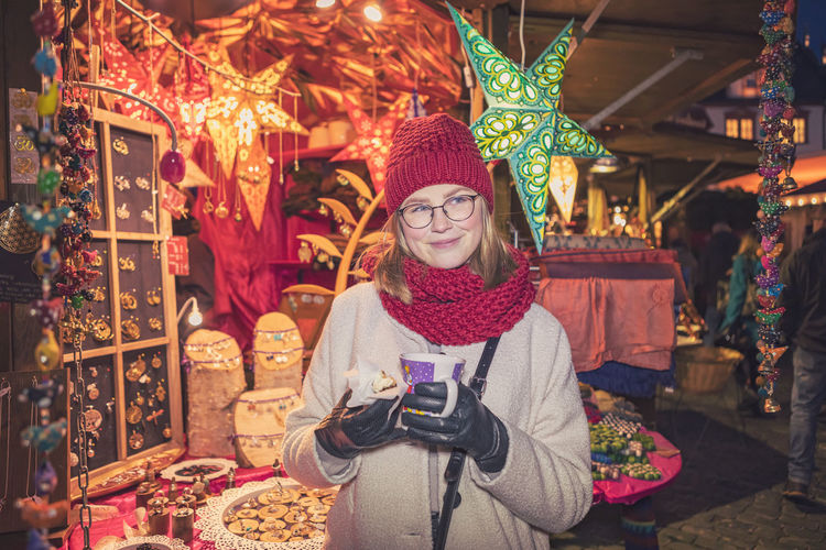 Young woman standing in market during christmas