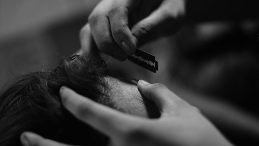 Close-up of person cutting hair with razor blade