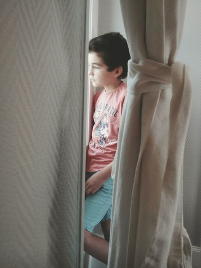Thoughtful boy standing by window seen through curtains