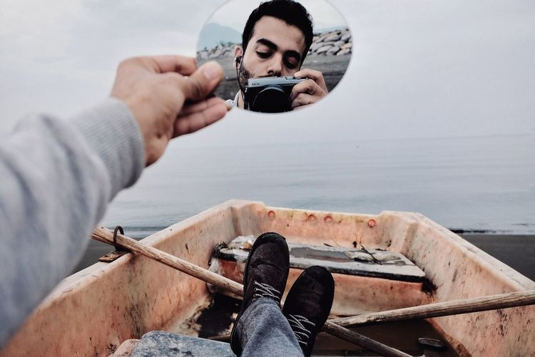 Low section of man holding mirror with reflection on boat at beach