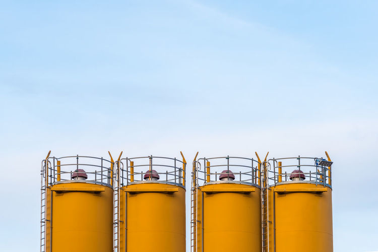 Four silos in front of blue sky Factory Industry Sky Metal Low Angle View No People Storage Tank Day Outdoors Side By Side Copy Space Blue Silo Yellow Container Railing Business Industrial Equipment Steel Alloy Minimalism Minimal Construction Site Business Estate My Best Photo