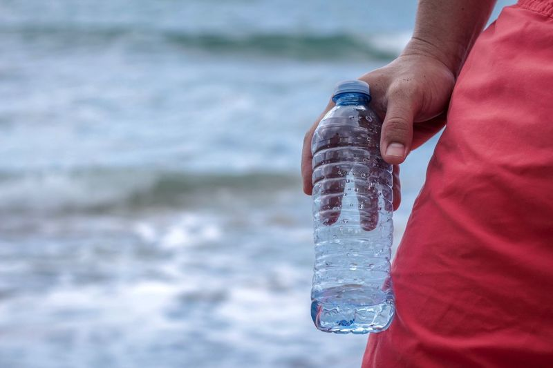 Close-up of man holding plastic bottle against sea