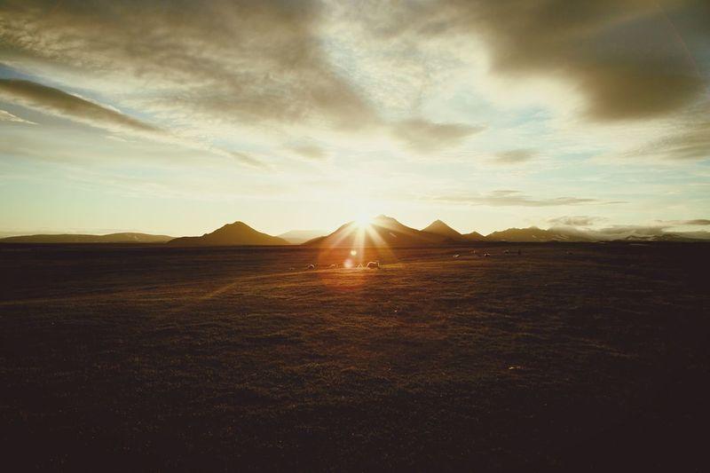 Sun shining through clouds over mountain