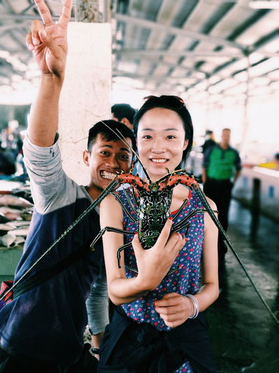 Portrait of smiling friends holding sea animal while standing at market
