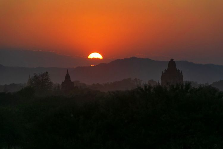 Silhouette of temple against buildings during sunset