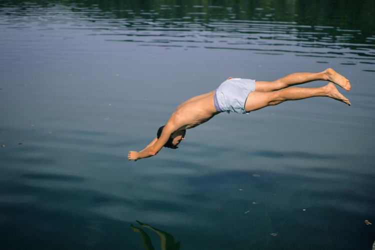 Shirtless man jumping in lake