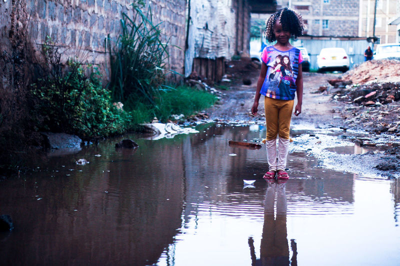 Girl Standing In Puddle On Pathway By Building