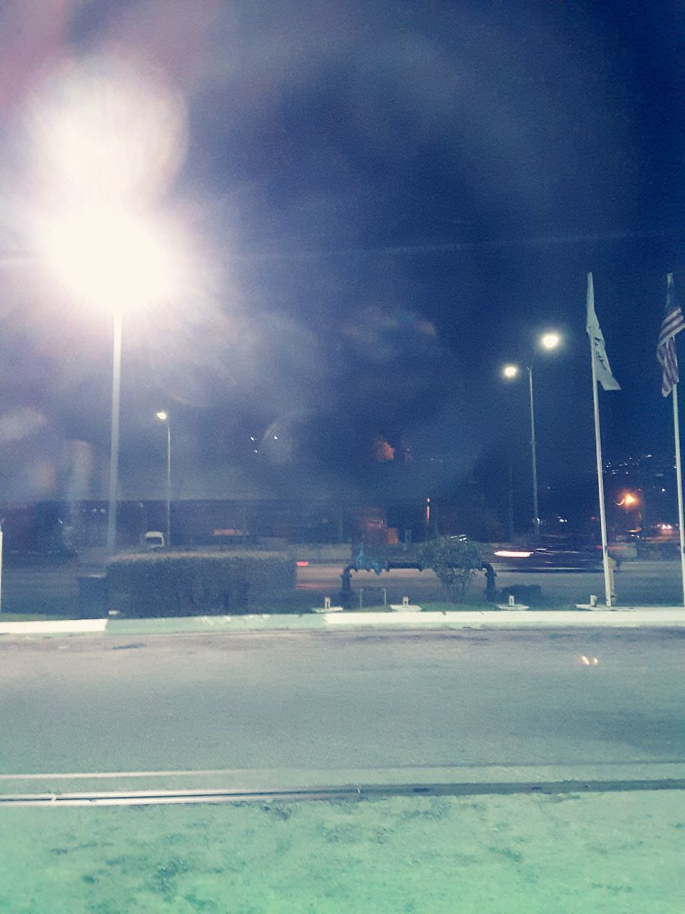 illuminated, lens flare, street light, night, transportation, road, street, car, outdoors, building exterior, sky, land vehicle, built structure, no people, high street, architecture, city, nature