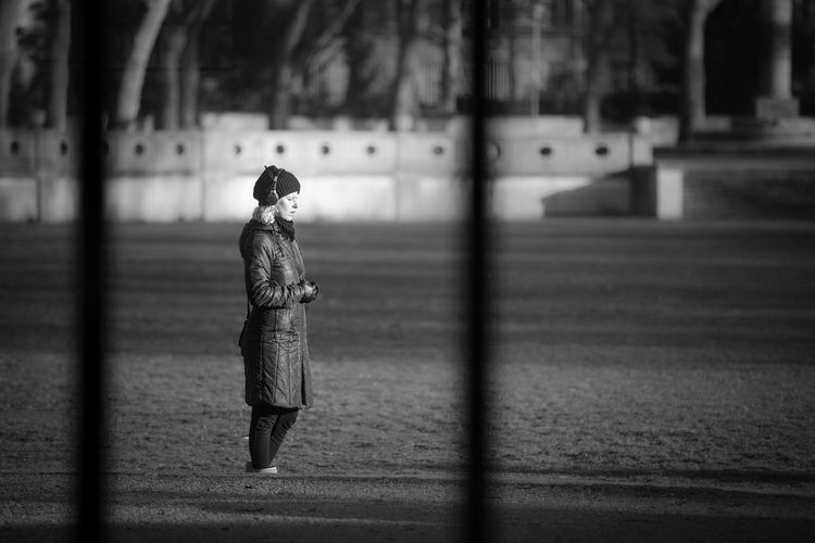 Woman mediating in park or simply enjoying the winter sun Alone Black & White Black And White City City Life Day Depth Of Field January Lifestyles Looking Through Window Mediation One Person Park Real People Selective Focus Showcase: January Standing Streetphotography Sunny Day Winter Woman