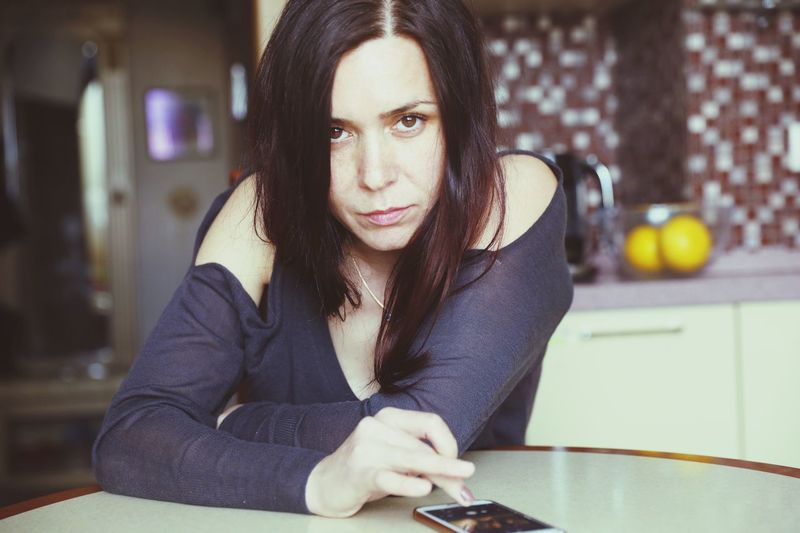 Portrait Of Beautiful Woman Using Mobile Phone At Home