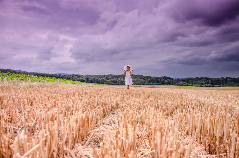 Girl standing amidst agricultural field against cloudy sky