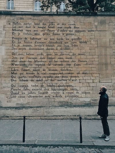 Full length of man standing by text on wall