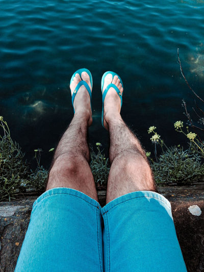 Low section of man relaxing by lake