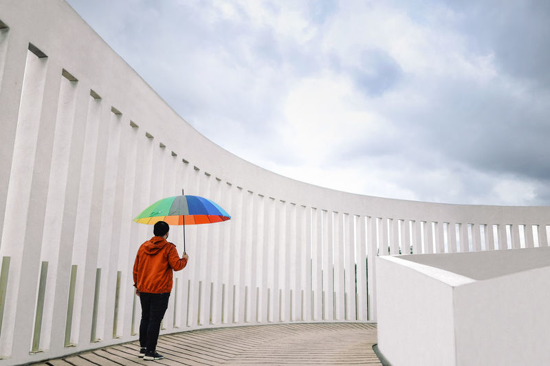 Full length of man standing with an umbrella against sky