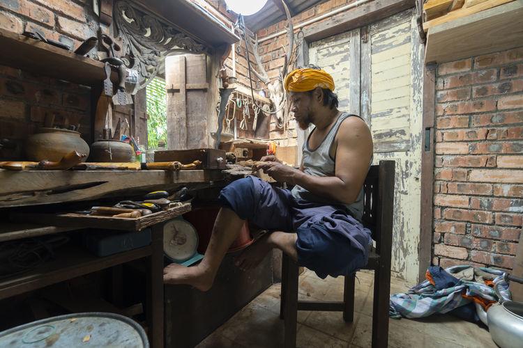 Man sitting on chair in workshop