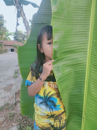 Girl looking away while standing outdoors