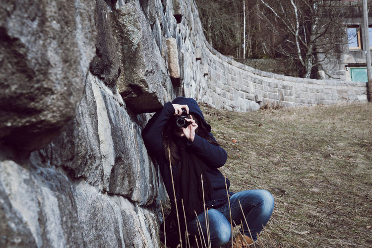 Woman Photographing While Crouching By Retaining Wall