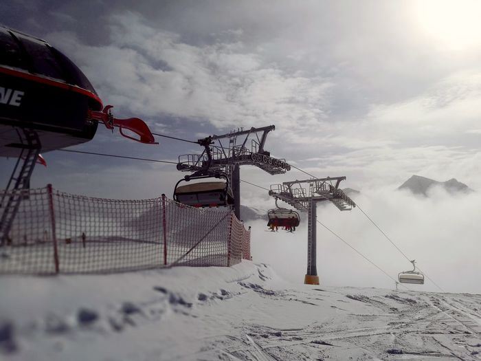 Low angle view of overhead cable cars against cloudy sky during winter