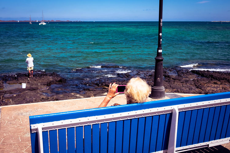 Old woman taking mobile picture of a fisherman on a bench