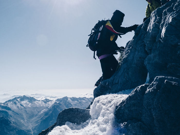 Side view of person rock climbing against clear sky during winter