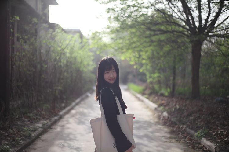 Portrait of young woman with shoulder bag standing on road amidst trees