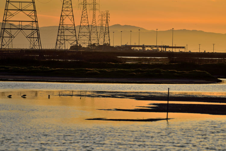 Silhouette electricity pylon by sea against sky during sunset