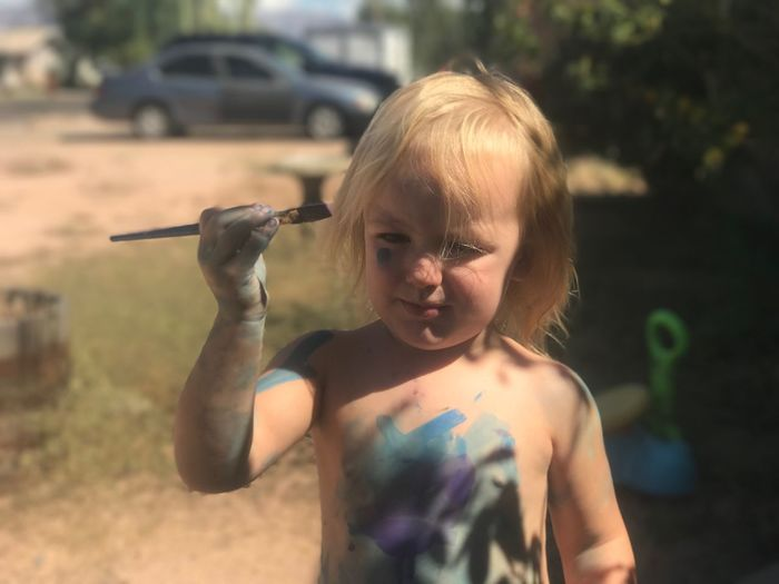 Close-up of shirtless girl with paintbrush