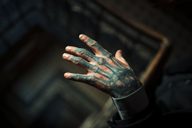 Cropped hand of young man with tattoo over spiral staircase