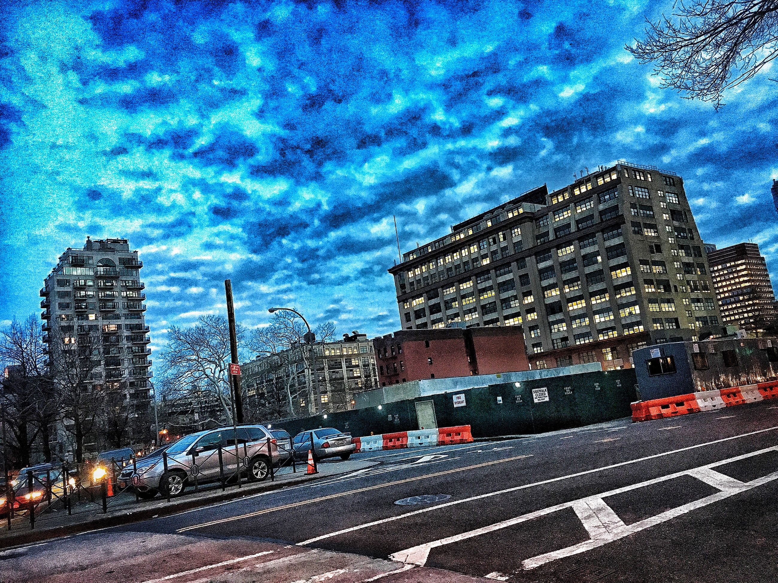 sky, cloud - sky, building exterior, transportation, architecture, built structure, city, car, land vehicle, cloudy, road, street, cloud, blue, mode of transport, dusk, no people, city life, outdoors, illuminated