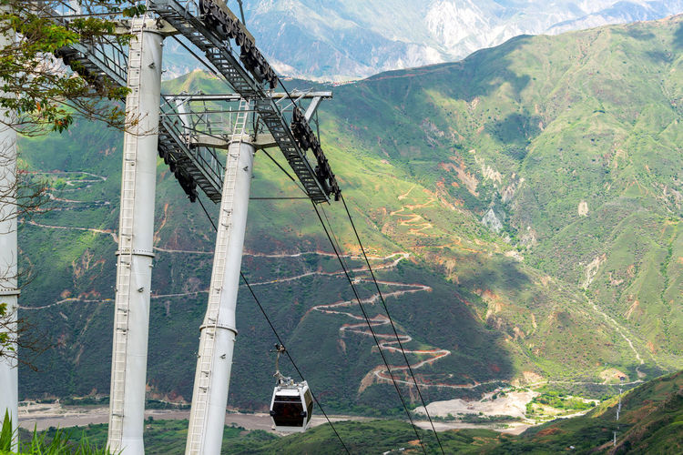 Aerial tram with a view of Chicamocha Canyon in Santander, Colombia in the background Chicamocha Canyon Cliffs Colombia Green Nature Panachi Santander Scenic Travel Tree Trees View Aerial Bucaramanga Canyon Chicamocha Landscape Mountain Mountains Outdoor Park River Tourism Vacation Wire