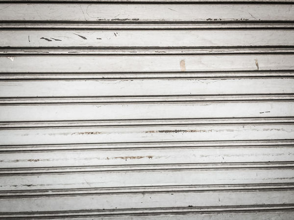 Vintage old roller shutter garage door. Grungy metallic roller shutter door for background. Backgrounds Close-up Closed Corrugated Corrugated Iron Day Dirty Full Frame Garage In A Row Iron Metal No People Outdoors Pattern Protection Repetition Safety Shutter Shutter Door Textured  Textured Effect Wall - Building Feature Weathered Wood - Material