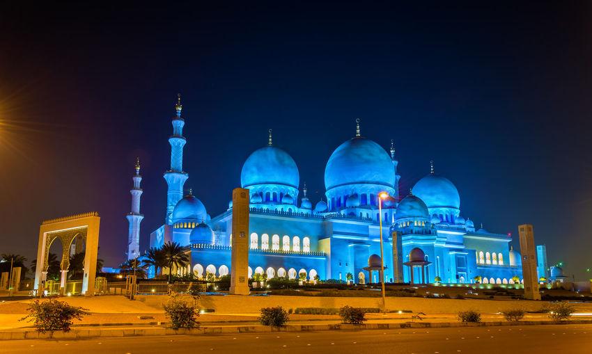Illuminated building against blue sky at night