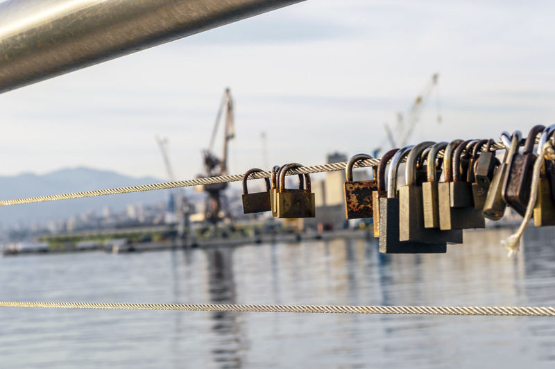 Close-up of padlocks on river against sky
