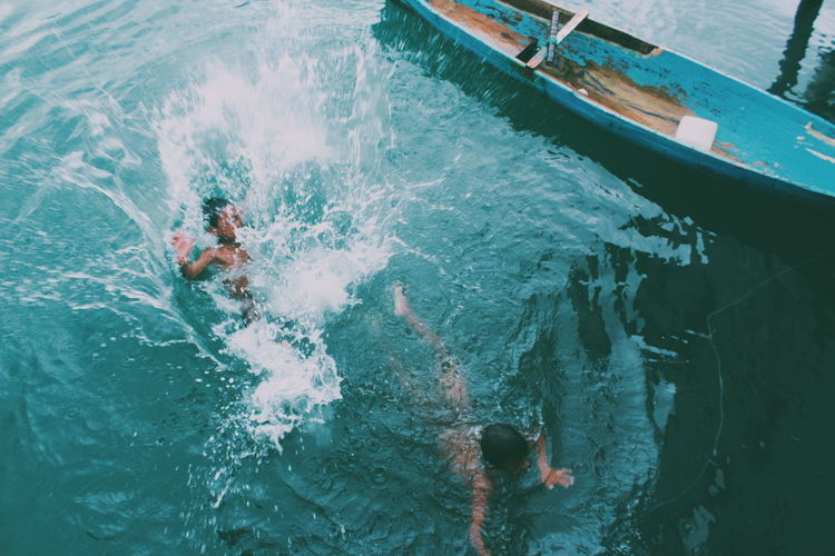 High angle view of boys swimming by boat on lake