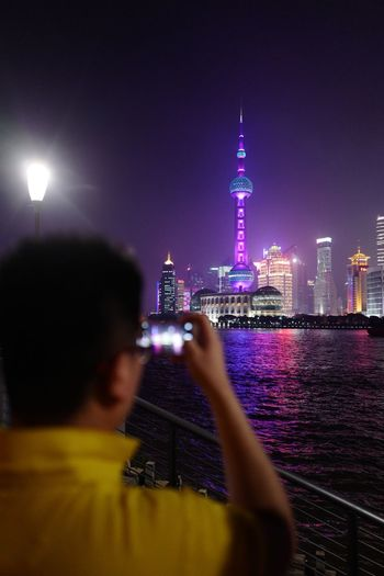 Taking photos of tourists taking photos Architecture Built Structure Night Building Exterior City Illuminated Sky Cityscape Office Building Exterior Skyscraper Tall - High Building One Person Tower Lifestyles Nature Rear View Travel Destinations Real People Modern A New Perspective On Life