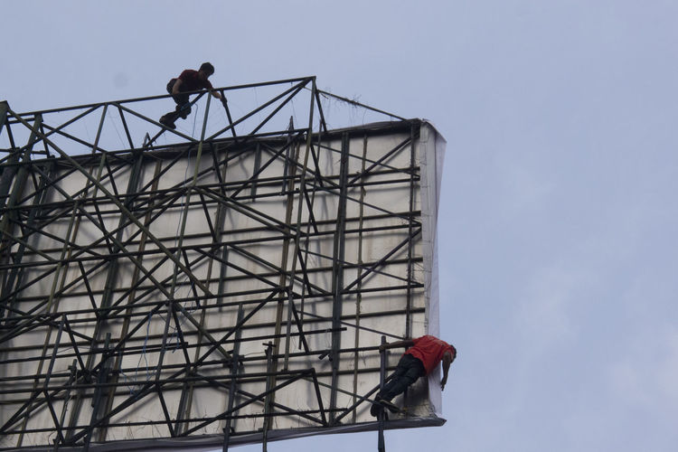Low Angle View Of Men Working On Billboard Against Sky