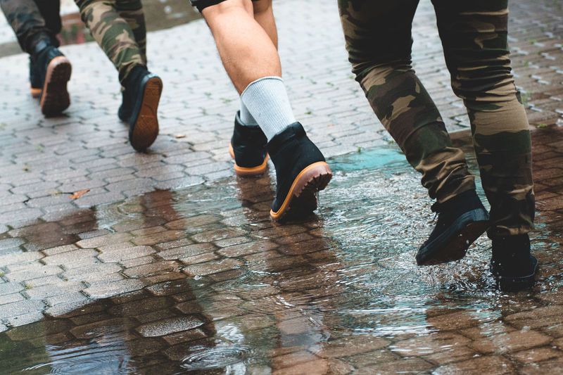Low section of men walking on wet walkway