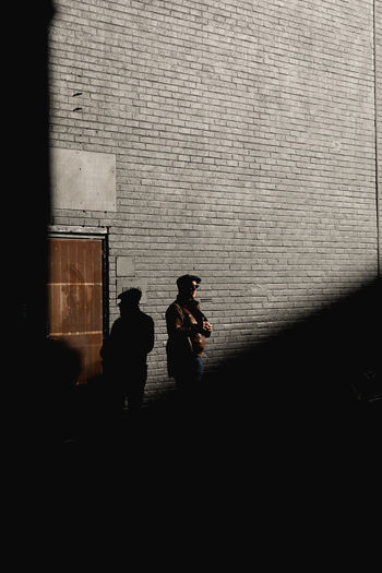 Architecture Built Structure Real People Wall - Building Feature Men Standing Building Exterior People Two People Walking Silhouette Full Length Wall Lifestyles City Day Outdoors Adult Leisure Activity Brick Wall Brick Smoking Shadow Light And Shadow Travel Destinations Capture Tomorrow
