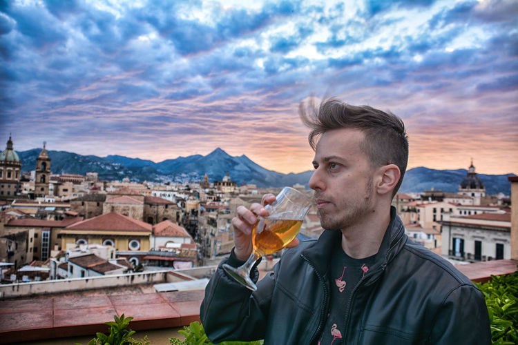 Young man drinking wine against buildings in city