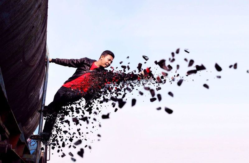 Digital composite image of man getting scattered while climbing on train against clear sky