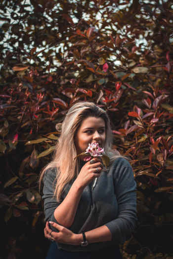 Smiling young woman with flower standing against trees