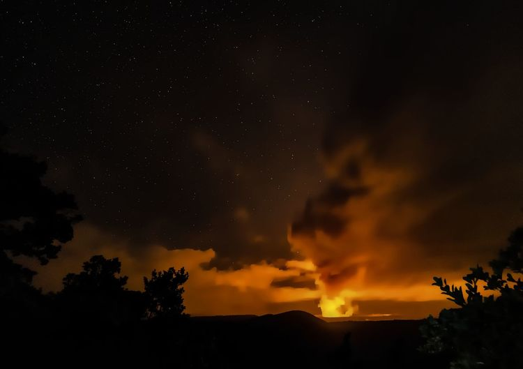 Kilauea Iki in the foreground looking to the caldera lava lake in Hawaii Volcanoes National Park Hawaii Hawaii Life Nightphotography Smoke Beauty In Nature Burning Clouds Clouds And Sky Fire Flame Lava Nature Night Nightshot No People Outdoors Scenics Silhouette Sky Stars Tree Volcanic Landscape Volcano