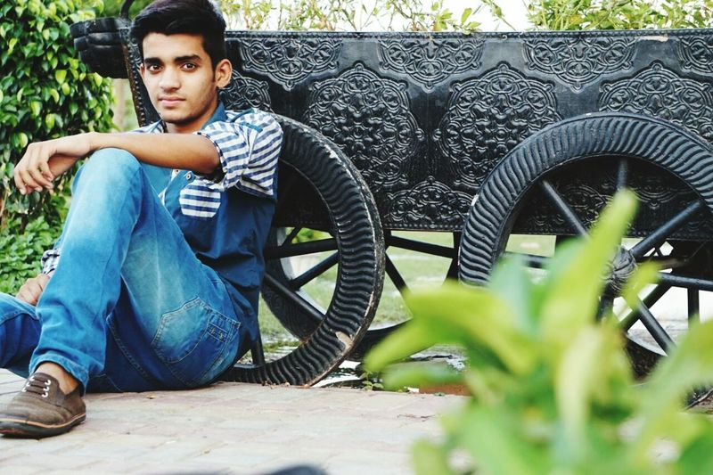 Portrait of young man sitting by cart at park