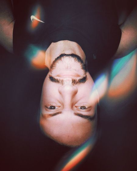Upside down portrait of man with lens flare