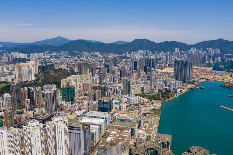 Aerial view of sea and buildings in city against sky