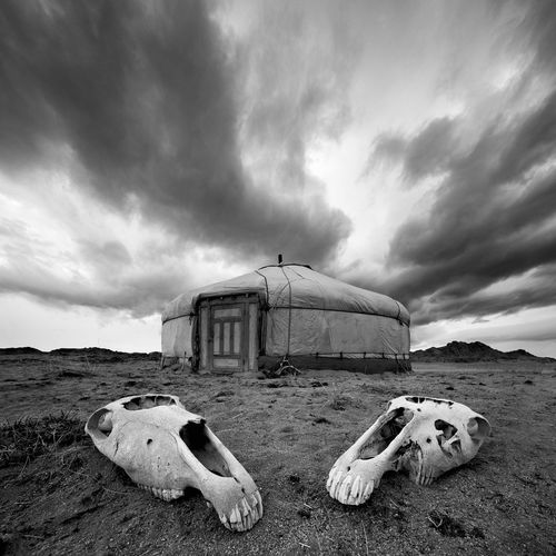 Abandoned built structure on beach against cloudy sky