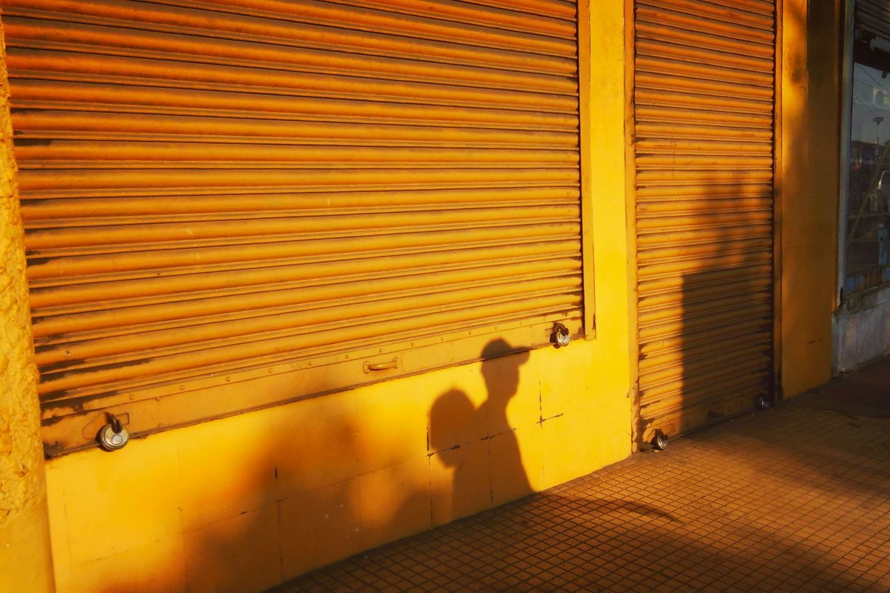 yellow, shutter, architecture, built structure, no people, building exterior, closed, sunlight, metal, outdoors, wall - building feature, day, security, shadow, protection, iron, pattern, corrugated iron, safety, window, focus on shadow