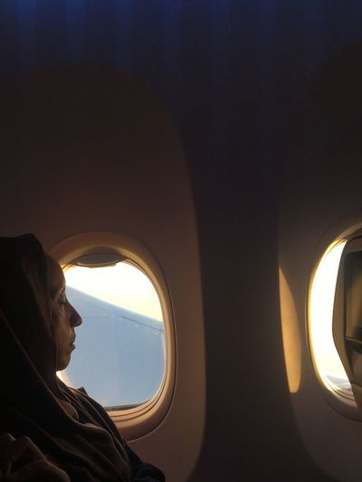 Side view of woman with eyes closed traveling by window in airplane