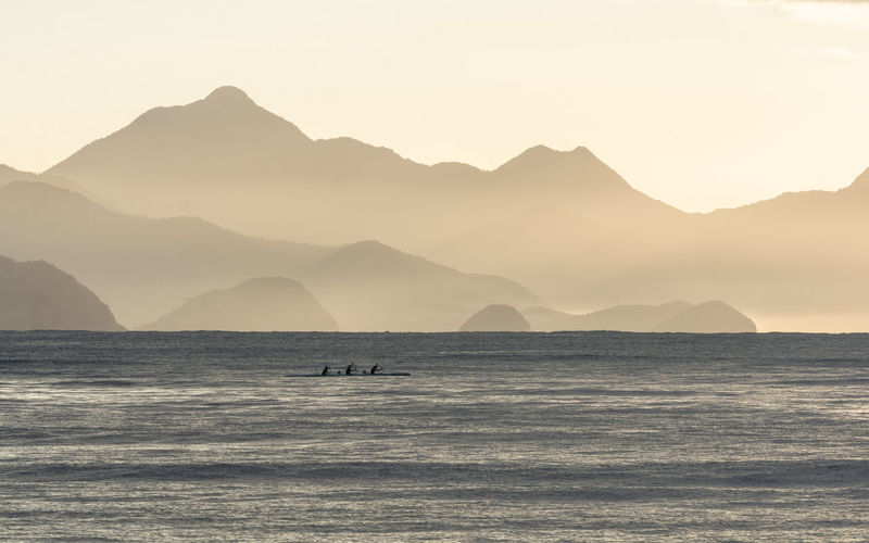 Scenic view of sea and silhouette mountains against clear sky